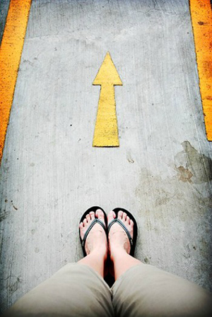 looking down at feet in flipflops standing in front of an arrow on the pavement pointing forward