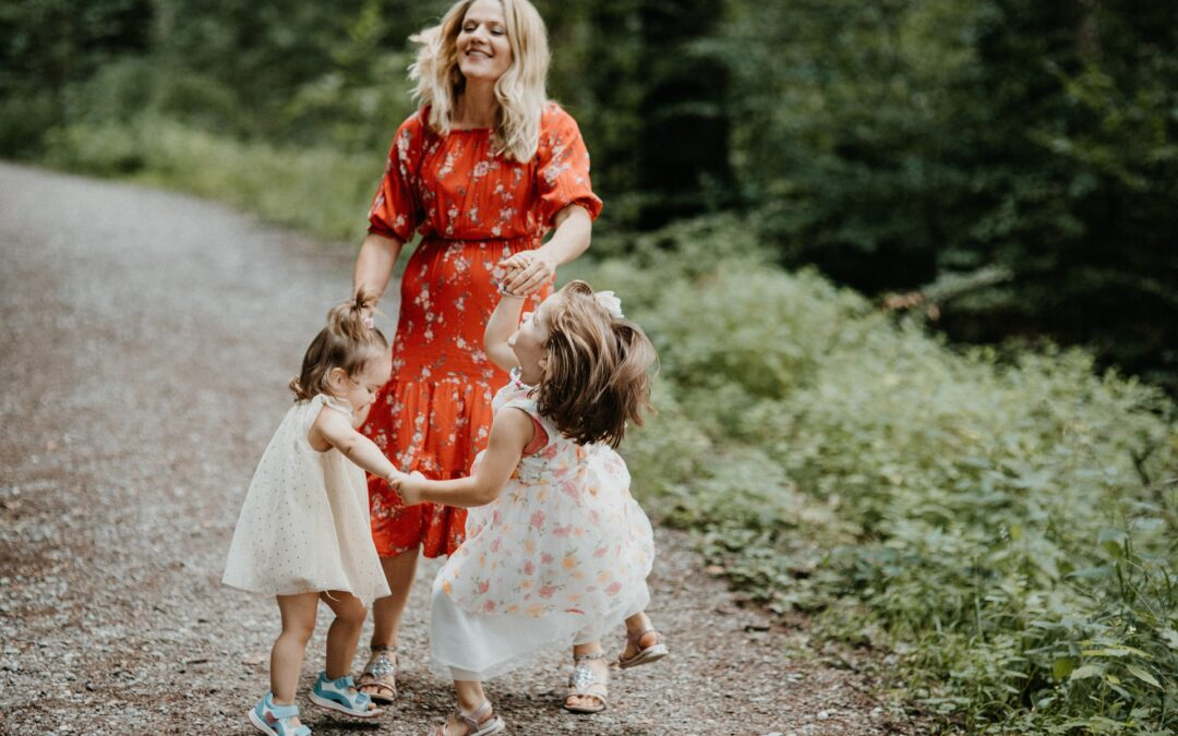 woman dancing in the woods with two young girls, all in sundresses