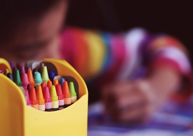 box of crayons with small child coloring in the background